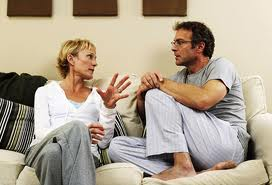 middle age couple talking on couch