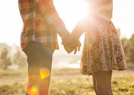 couple holding hands in the sunlight