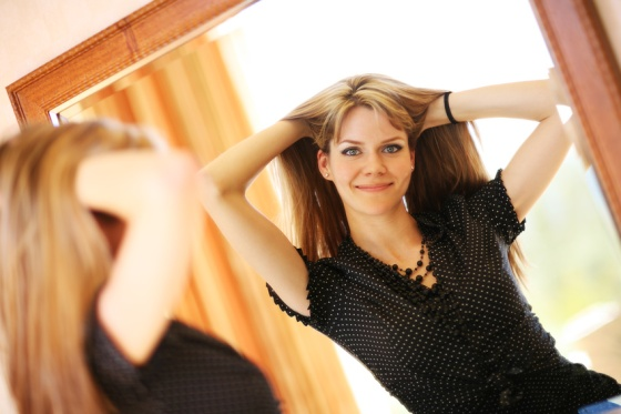 Beautiful young woman looking in the mirror