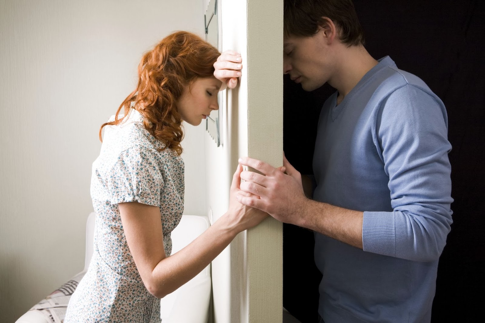woman and man with wall between but holding hands and heads against wall