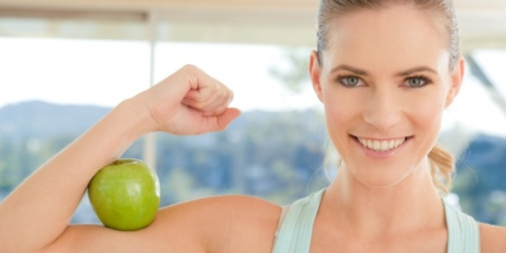 woman with apple on her bicep arm